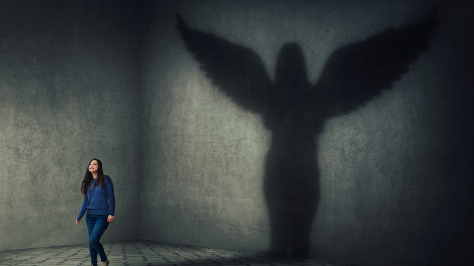 Proud and confident young woman walking and casting a superhero shadow as a guardian angel with wings on a dark room wall. Inner power, ambition and leadership concept.
