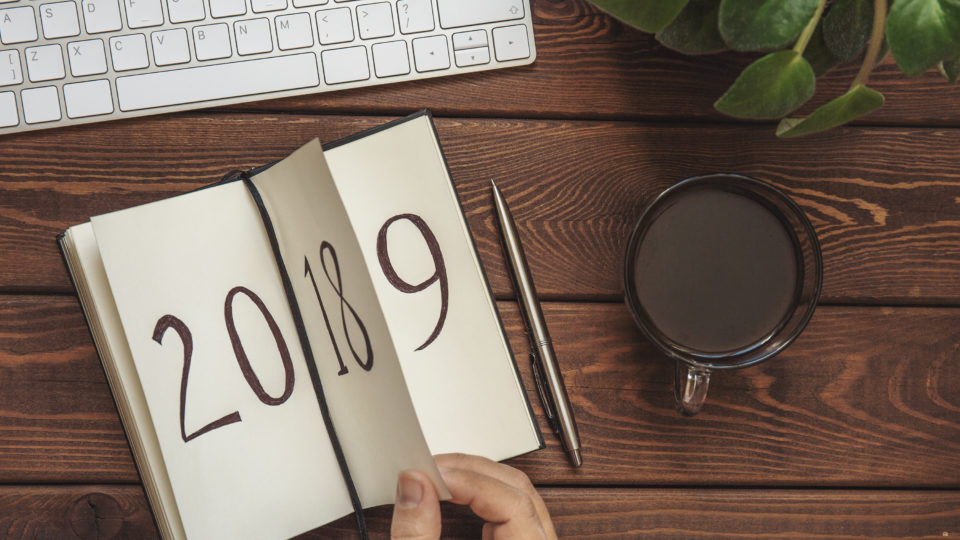 New Year 2019 is coming concept. Female hand flips notepad sheet on wooden table. 2018 is turning, 2019 is opening, top view, toned