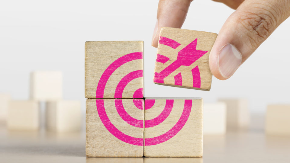 Hand putting the last piece of wooden blocks with the dart target icon. Goal, business goal, achieving a goal or success concept.